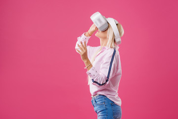 Young Blond happy woman student with virtual reality goggles. Studio shot on pink background. Virtual learning