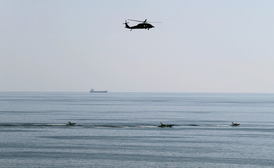 MH-60S helicopter hovers over Iranian Revolutionary Guards speed boats which are seen near the USS John C. Stennis CVN-74 as it makes its way to gulf through strait of Hormuz