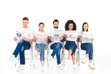 multiethnic group of young people sitting on chairs with crossed legs and reading newspapers isolated on white