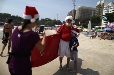 Paulo Mourao, who represents Santa Claus, poses for a photo with a child at the Copacabana beach in Rio de Janeiro