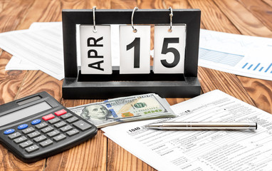 Date of 15 april on rollover calendar on the table with tax form, money and calculator. Time to pay tax.