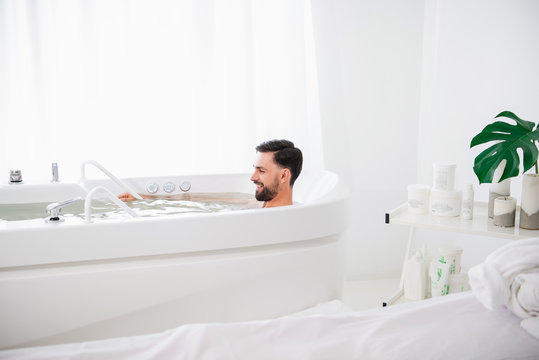 Positive man relaxing in hydro massage bathtub and smiling cheerfully