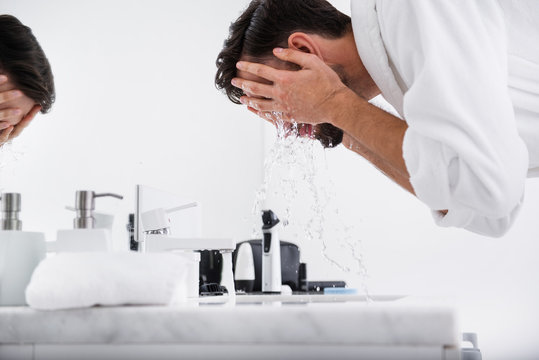 Close up of bearded man washing his face in bathroom