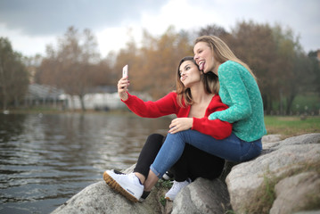 Friends taking a selfie, sitting next to the lake