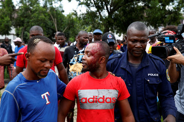 A man who was injured before an election event of Felix Tshisekedi is escorted by police officers in Kinshasa