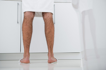 Man in white bathrobe standing in front of the drawer unit