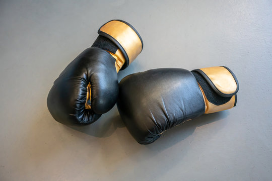 Old black and yellow boxing gloves on grey concrete background.