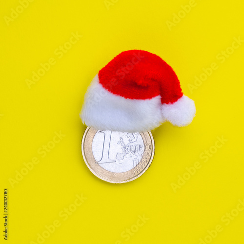 4930d39f1a006 The concept of financial costs of the European New Year and Christmas. Coin  one euro in a red santa claus hat on a yellow background.