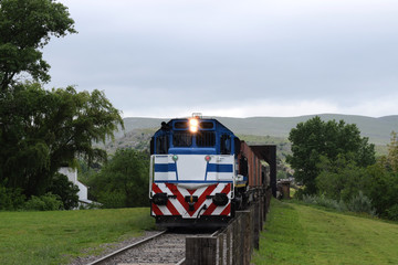 freight train rides on the rails of the mountains in the afternoon in overcast weather