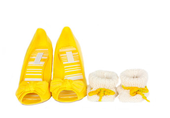 Women's yellow shoes and knitted baby booties on white, isolated close-up background. Two pairs of shoes. Mother's day celebration. Copy space. Free space for text. Horizontal image.