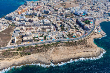 Seaside cliffs, colourful houses and streets of Qawra town in St. Paul's Bay area in the Northern Region, Malta. Popular tourist resort between Bugibba and Salina. Aerial view. Malta island from above