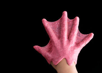 The hand of the child is covered with pink mucus. The game is slime.
