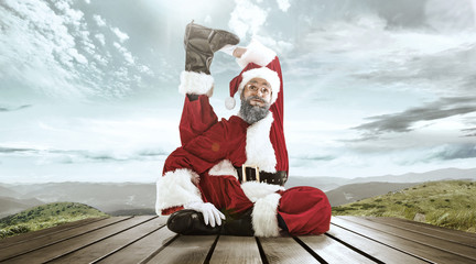 Santa Claus in traditional red white costume in front of white snow winter landscape panorama. Christmas, x-mas, gifts concept.