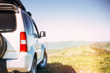 Car travel concept. Blurred back side of SUV car on the green mountain top with focus on distant road and hills in clear sunny day