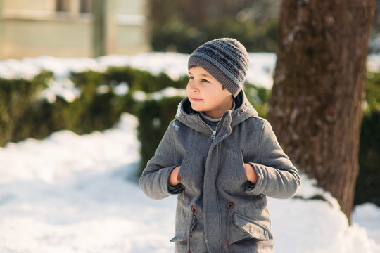 Boy walkink in the park at winter holiday. Christmas mood