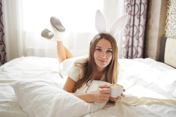 lovely brunette girl with bunny ears on her head and lying with coffee on a bed in her bedroom