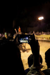Woman recording night scene of a party with a mobile