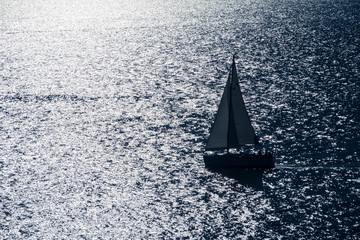 silhouette of a sailboat in open sea and bright reflecting sunlight
