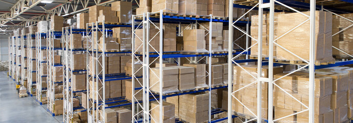 Boxes with goods on shelves in a large distribution warehouse with metal racking storage system
