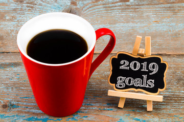 2019 goals on blackboard  with a cup of coffee, on wooden background.  New Year resolutions concept