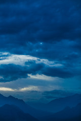 Amazing night landscape of calm clouds, blue sky and silhouettes of high mountains. Vertical color photography.