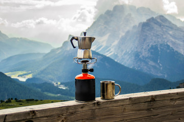 Outdoor cooking equipment or coffee making concept. Scenic landscape view of small silver mug and kettle/mokka pot standing on gas stove. Beautiful morning scene up in the Dolomites mountains, Italy