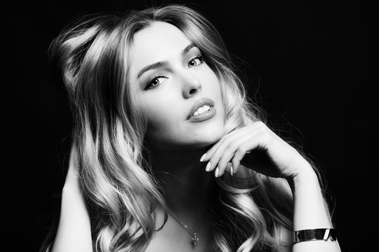 Beautiful young woman with long blond hair, black and white portrait, close-up