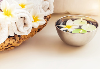 Rolled towels, candles and frangipani flowers.