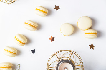 Yellow lemon macaroons on a white background next to golden Christmas decorations and asterisks. Festive tender French dessert. Top view, flat lay