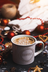 Closeup of a Cup of coffee or cocoa on a black background with Christmas red toys and a sweater