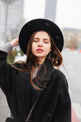 Young fashion woman walking on the city street wear black hat look around and smile to camera. Copy space. - Image