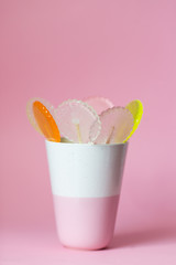 multi-colored lollipops on a pink background in a ceramic cup,