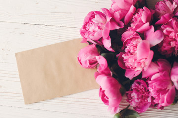 lovely pink peonies with empty craft card on rustic white wooden background top view, space for text. floral greeting card mock-up. beautiful flowers. happy mothers day concept