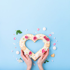 Valentine's Day heart-shaped cake with flowers as decoration. The concept of a gift to a loved one on a holiday.