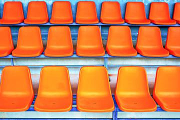 three rows of empty orange seats in a stadium, tennis courts, football