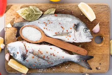 Two sea fish with flavored seasonings lie on a wooden board with a large wooden spoon of salt. Cooking process. View from above