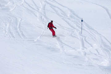 Snowboarder downhill on snowy off-piste slope