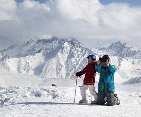 Happy little skier with father makes selfie on tablet device in snowy winter mountains