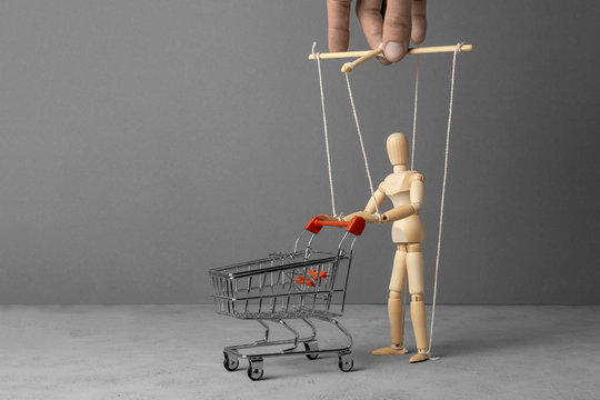 Control over the behavior of the buyer. Man with a shopping trolley from the supermarket like doll led by puppeteer. Copy space for text.