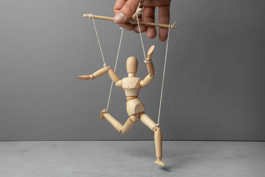The puppeteer holds the doll by the rope. The doll does not obey the puppeteer.