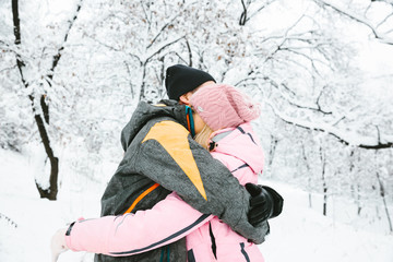 young people embrace one another in winter forest