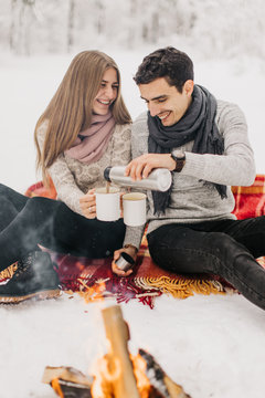 young couple on a date in the winter forest is heated by the fire and drink cocoa