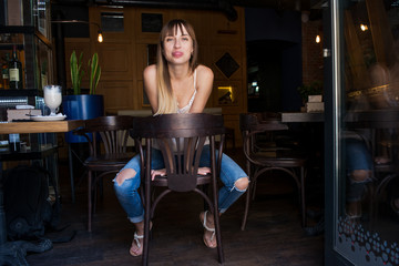 young pretty cute girl sitting in a cafe on a chair in jeans emotional pleasing and sexy