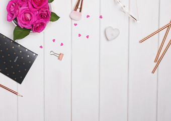 Creative frame with roses, feminine accessories and small paper hearts,