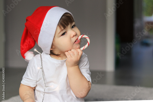 Cute Little Baby Boy In Red Santa Hat Eating Christmas Striped Candy