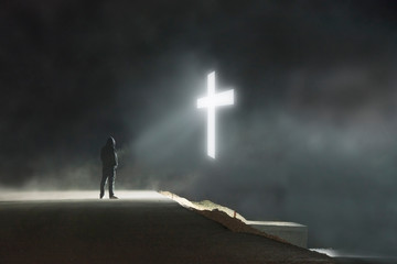 A concept digital art picture of a lone hooded figure lstanding on a road looking at a glowing cross floating in the sky on a misty dark night