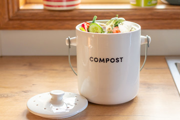 recycle kitchen food waste compost container full of kitchen waste on counter top, sustainable living concept