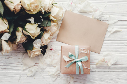 White roses with empty card and gift box on wooden background, flat lay with space for text. Floral greeting card mockup. Wedding invitation,happy mother day concept. Valentine day.