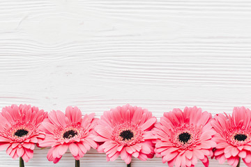 Pink gerbera on white  wooden background,  flat lay with space for text. Tender Floral greeting card mockup. Wedding invitation, happy mother day or Valentine day concept.