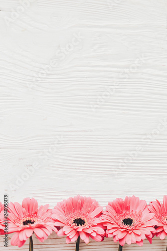 Pink gerbera on white  wooden background,  flat lay with space for text. Bright Floral greeting card mockup. Wedding invitation, happy mother day or Valentine day concept.